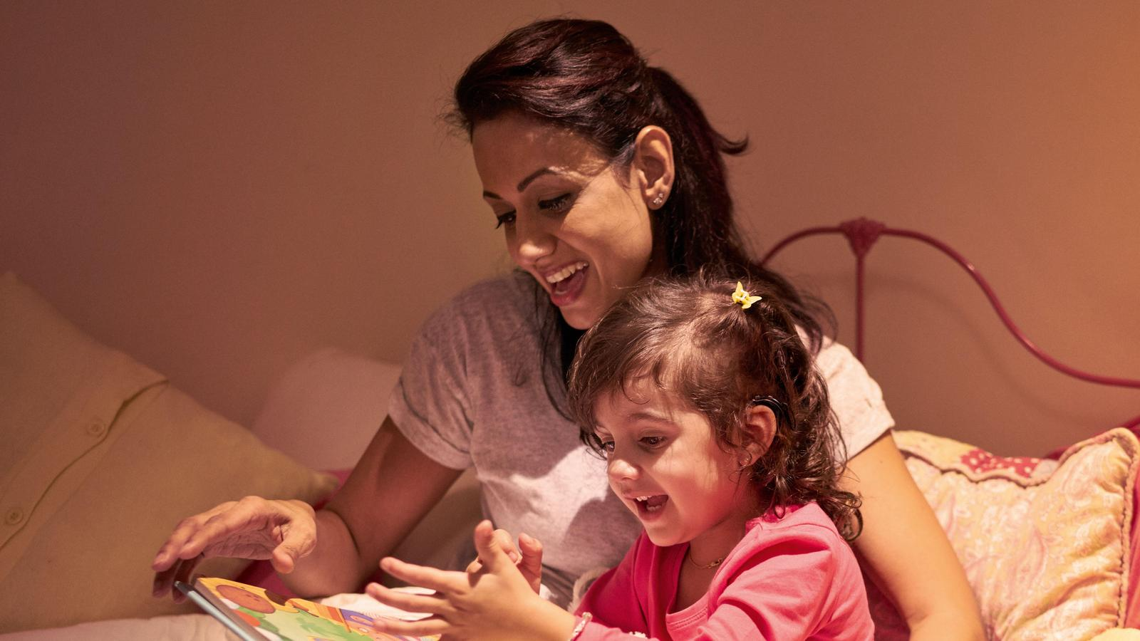 A child wearing an implant listens to her mother read a book