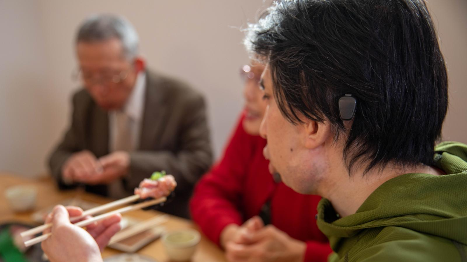 Cochlear recipient talks to a friend at a cafe