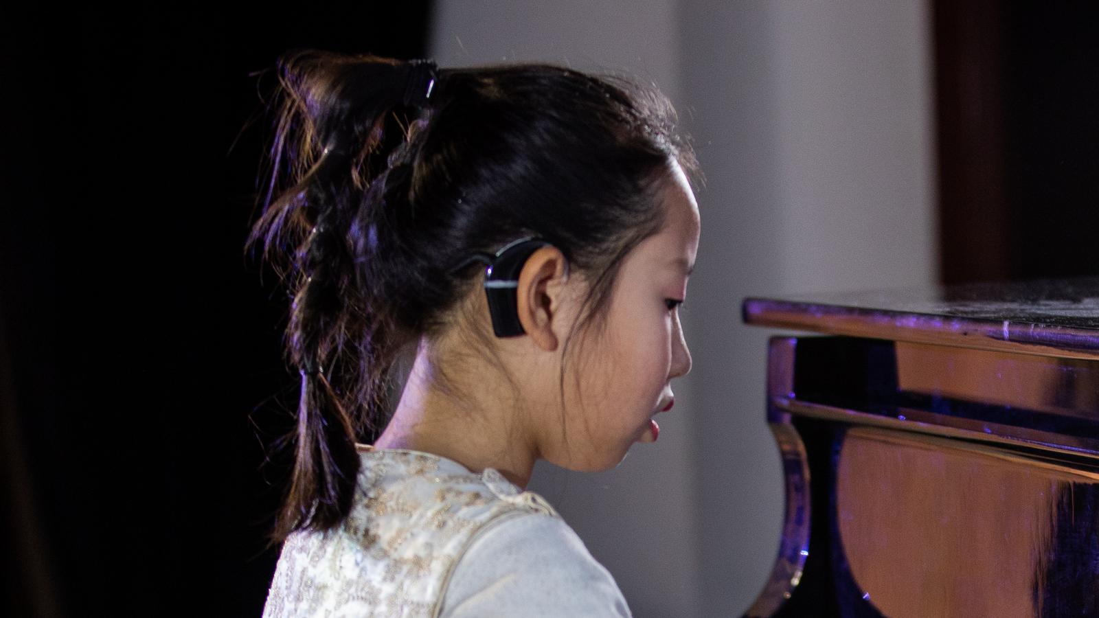 A girl wearing an implant plays the piano