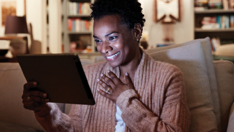 A woman smiles as she looks as a tablet
