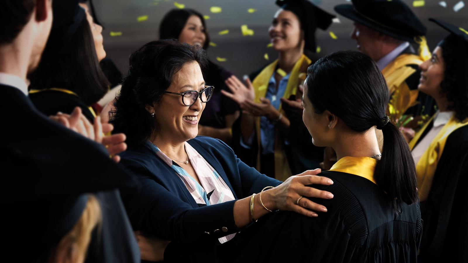 A woman smiles at her daughter during a graduation ceremony