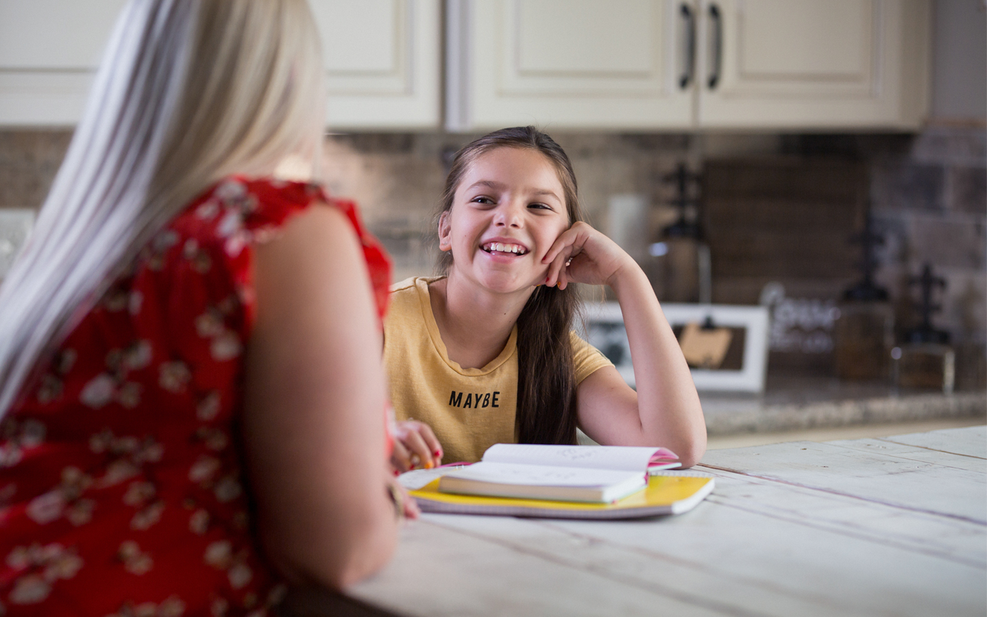 Cochlear recipient Holly doing homework at the kitchen with her mother