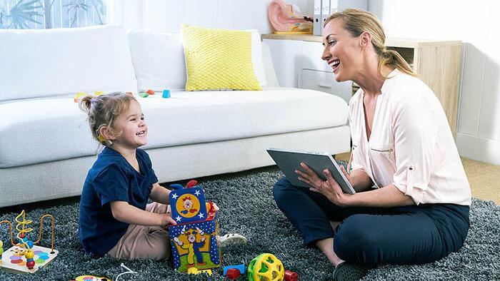 An audiologist sits on the carpet with a child Cochlear candidate