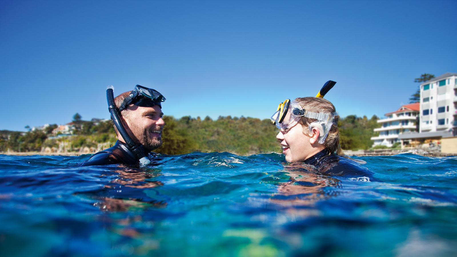 Een man draagt een Nucleus waterbestendig accessoire terwijl hij met een vriend gaat snorkelen