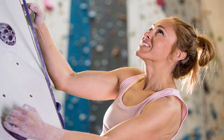 Mujer escalando que lleva el sistema Baha