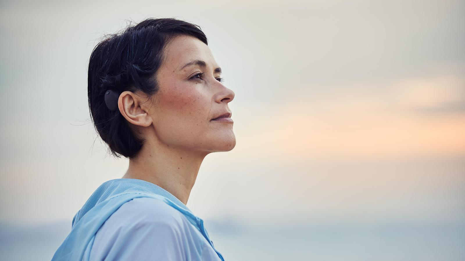 Head of caucasian woman looking into the distance and wearing an Osia implant