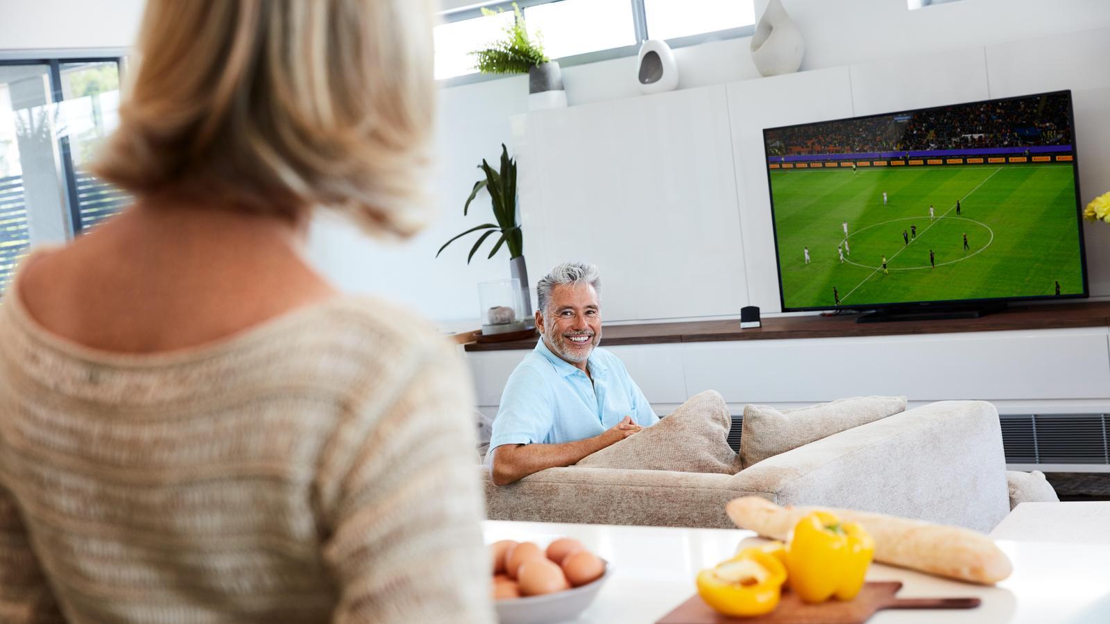 Hombre adulto viendo fútbol en la TV con Cochlear Wireless TV Streamer