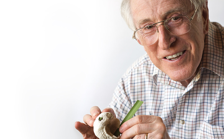 Professor Graeme Clark rijgt een grasspriet in een zeeschelp