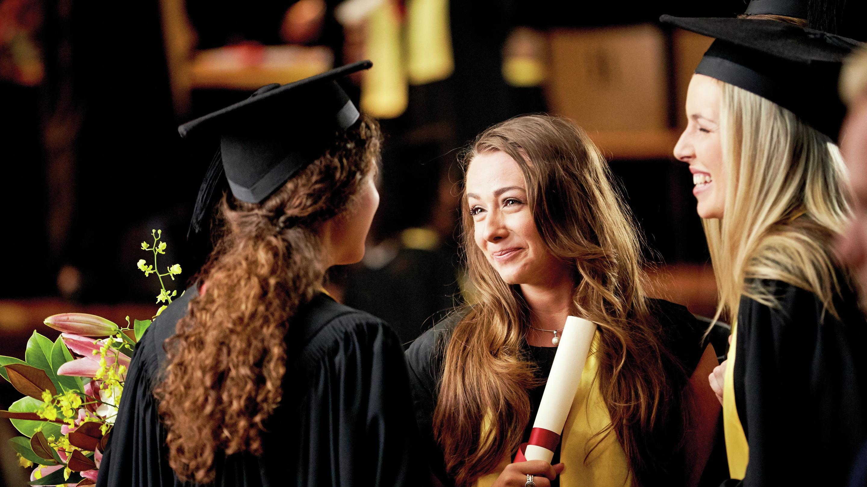 ثلاثة أصدقاء يتجاذبون أطراف الحديث بعد التخرج في الجامعة