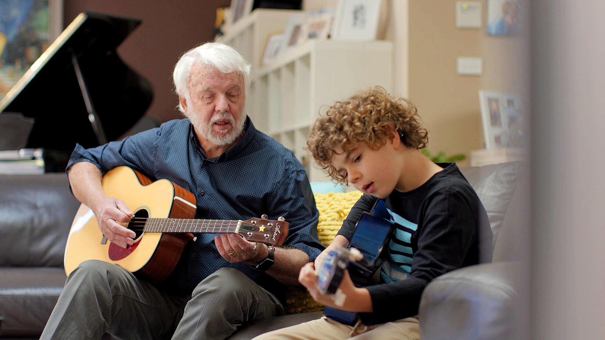 Ein Mann und ein Kind, das ein Cochlea-Implantat trägt, spielen Akustikgitarre