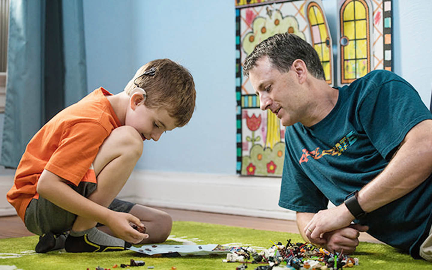 A boy with a Cochlear implant plays on the floor as his dad watches on