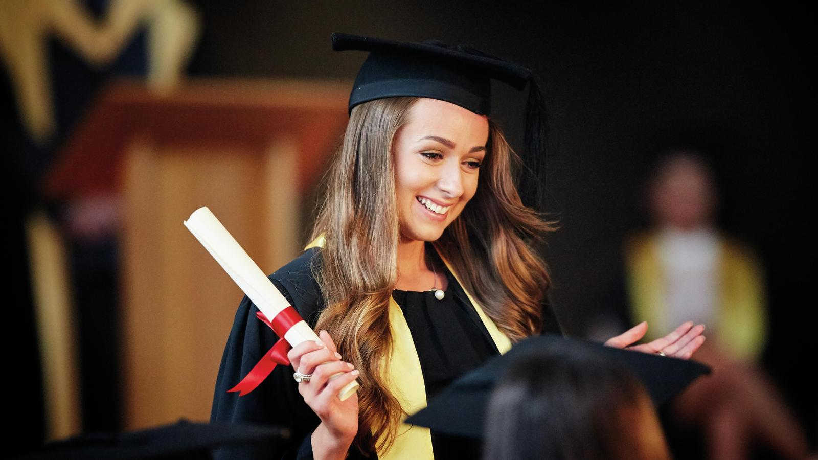 A woman wearing a mortarboard and gown holds a diploma