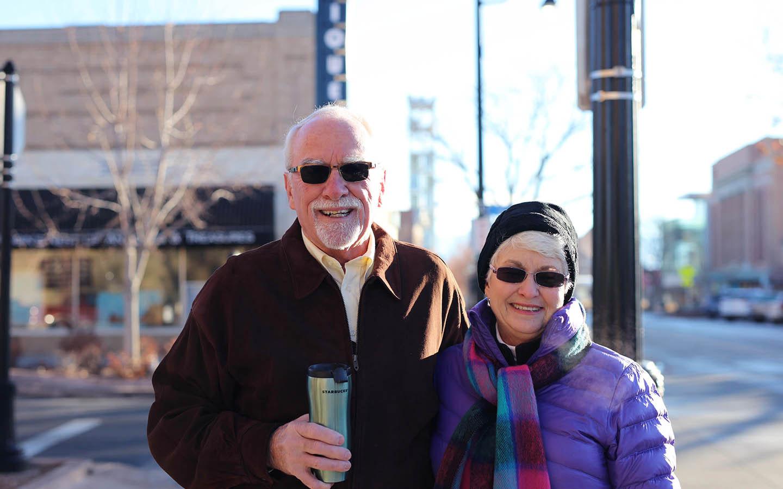 Cochlear-gebruiker Tom en zijn vrouw Brenda poseren op straat voor een foto