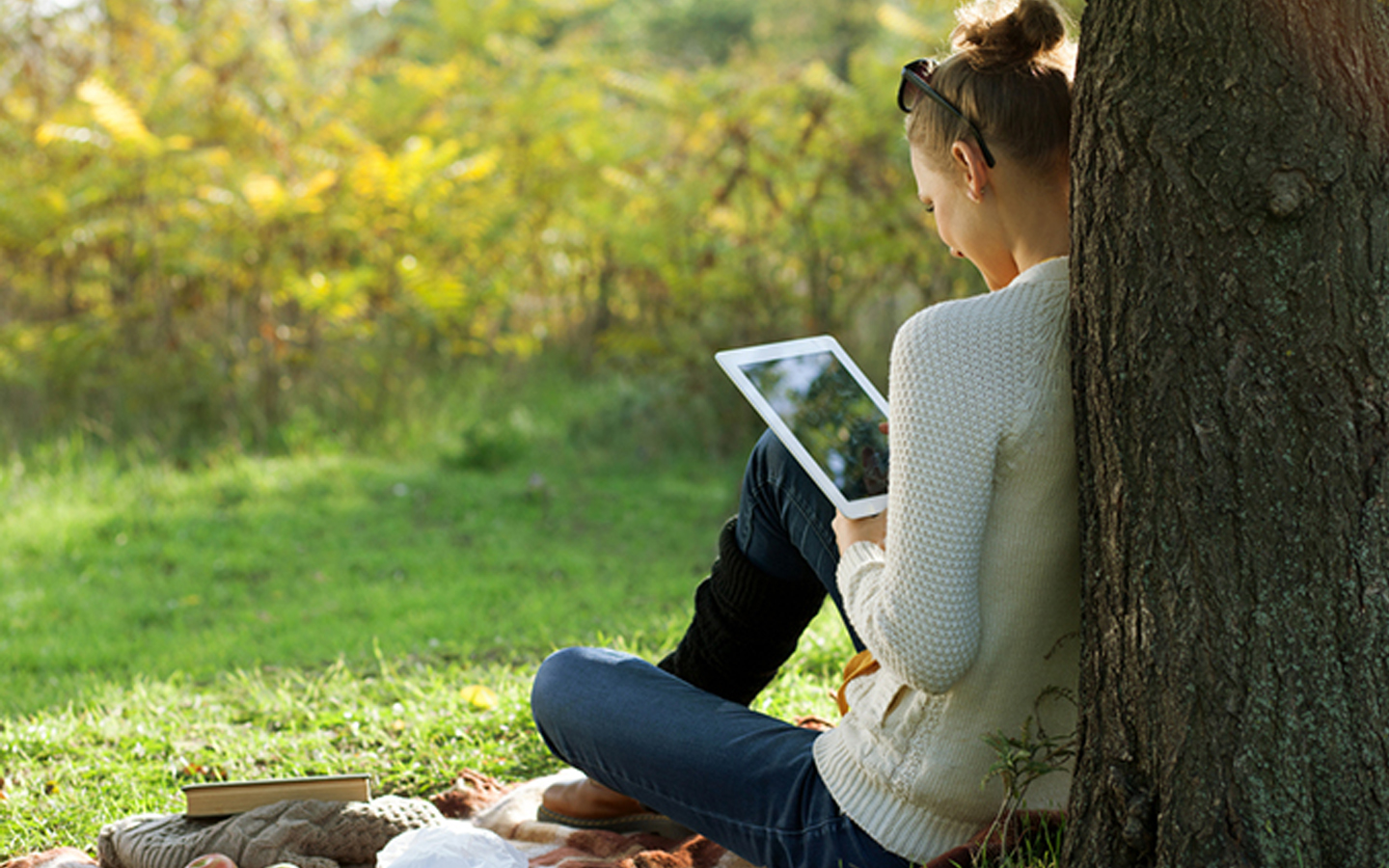 A woman reads from an iPad in the park