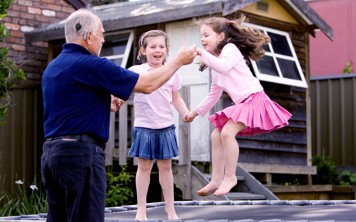 A Cochlear recipient holds his two grandaughters' hands as they jump on a trampoline