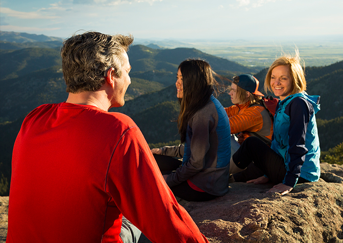 Recipient Mathias and his family sit together on a mountain top after their hike