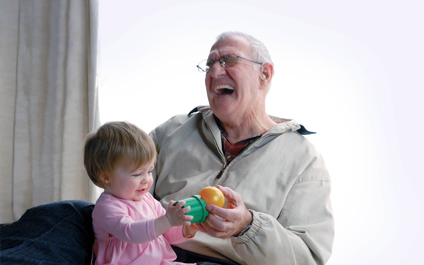 An elderly implant recipient laughs as his grandchild sits on his lap