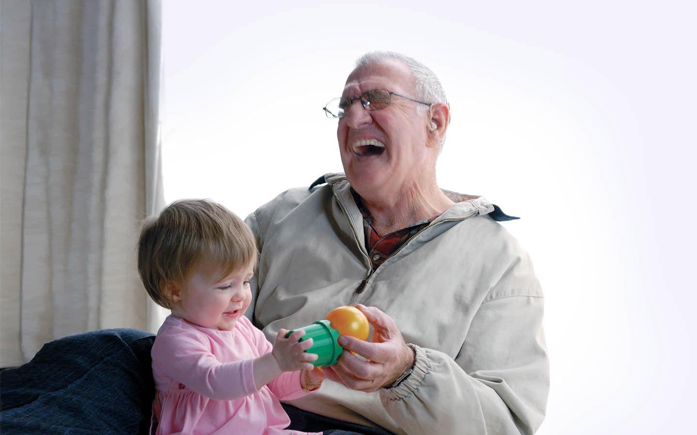 En äldre implantatanvändare skrattar medan hans barnbarn sitter i hans knä