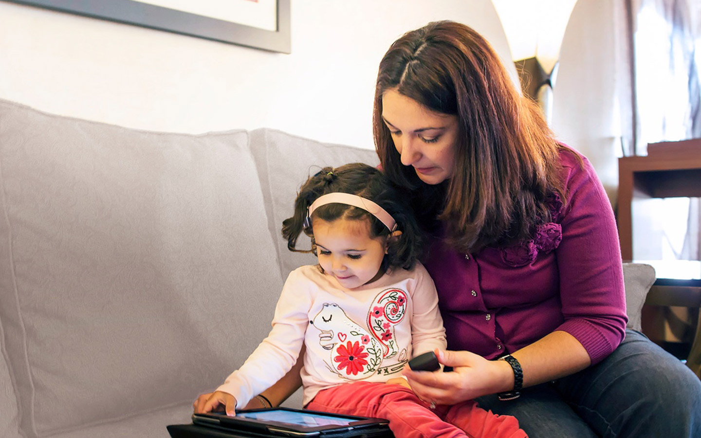 A woman reads with her young daughter on an iPad