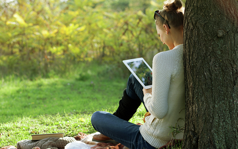 Žena si pod stromem čte z tabletu