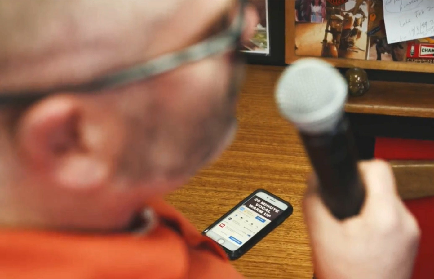Osia recipient Adrian adjusts his device settings with an iPhone while he sings karaoke