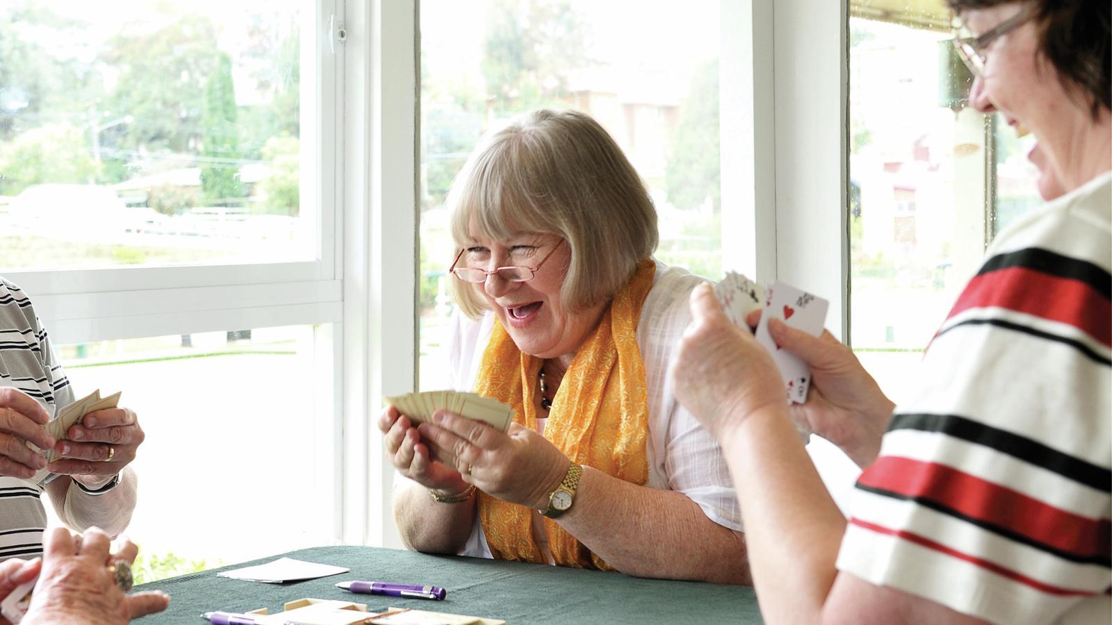 Cochlear-användaren Donna skrattar medan hon spelar kort
