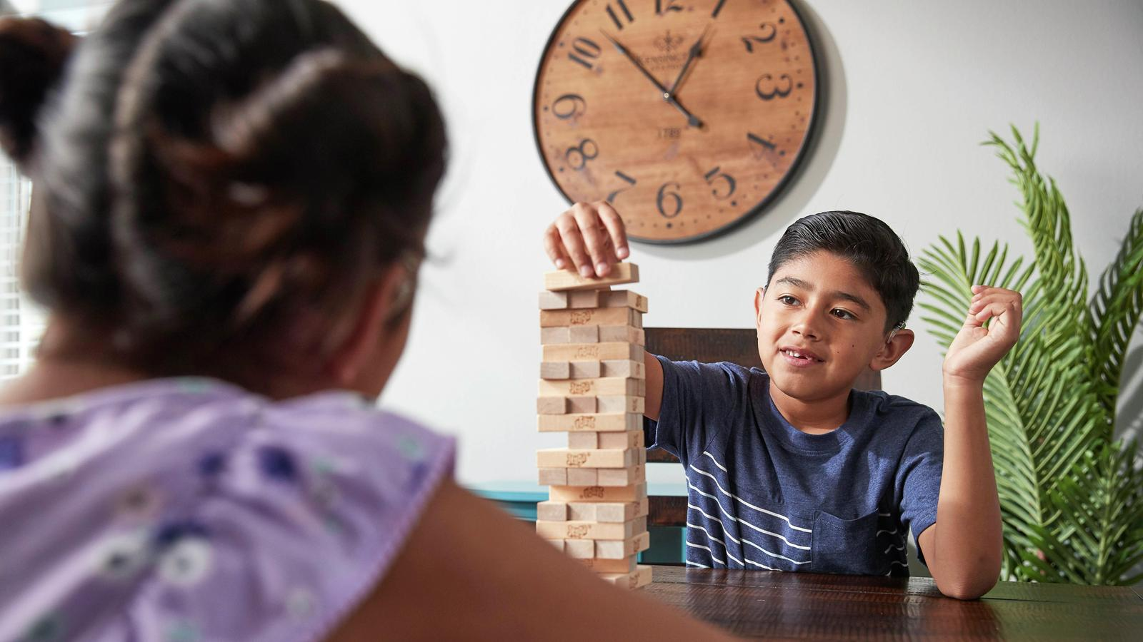 Cochlear recipient Kevin plays a block stacking game with a friend