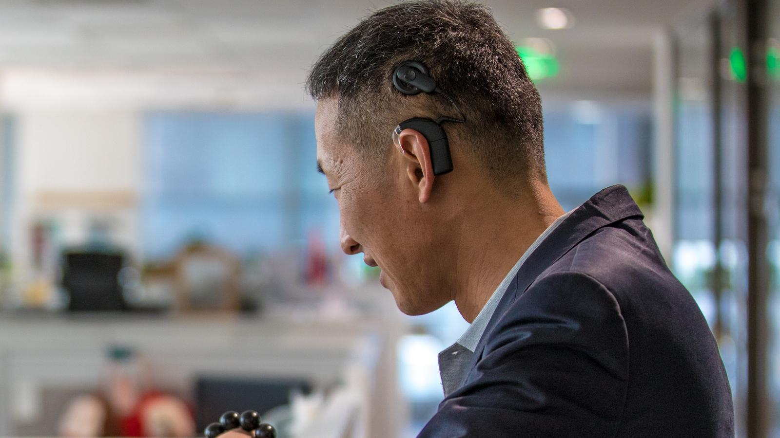 Kenneth laughs with coworkers as he wears his cochlear implants