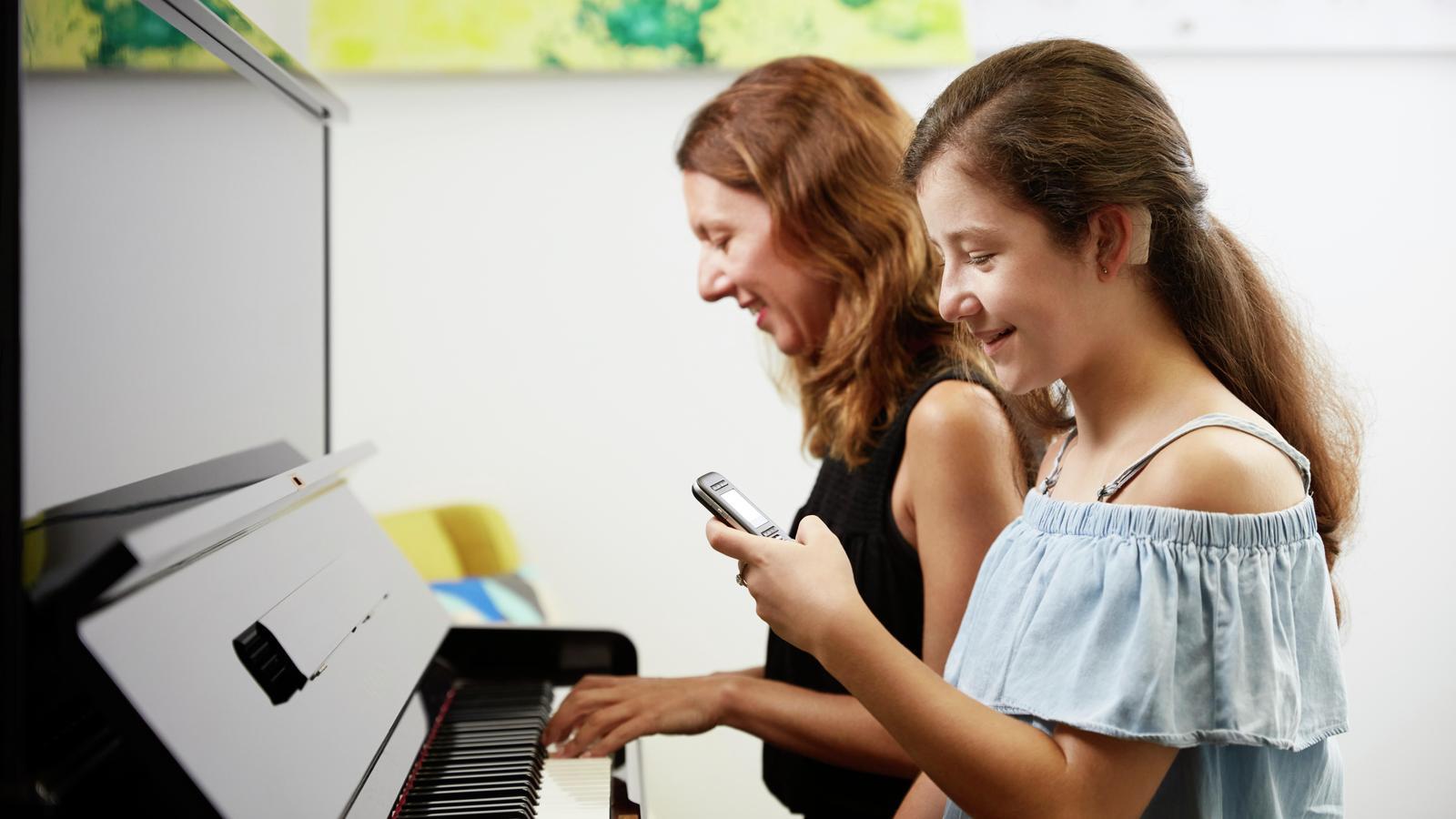 Chica adolescente usa un micrófono mientras su madre toca el piano