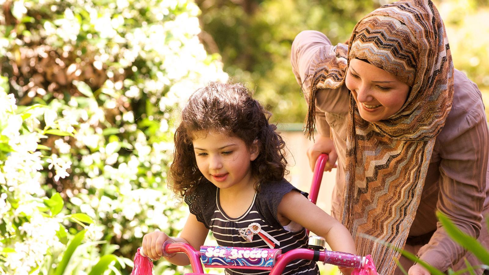 O femeie ajută o fată să meargă cu bicicleta