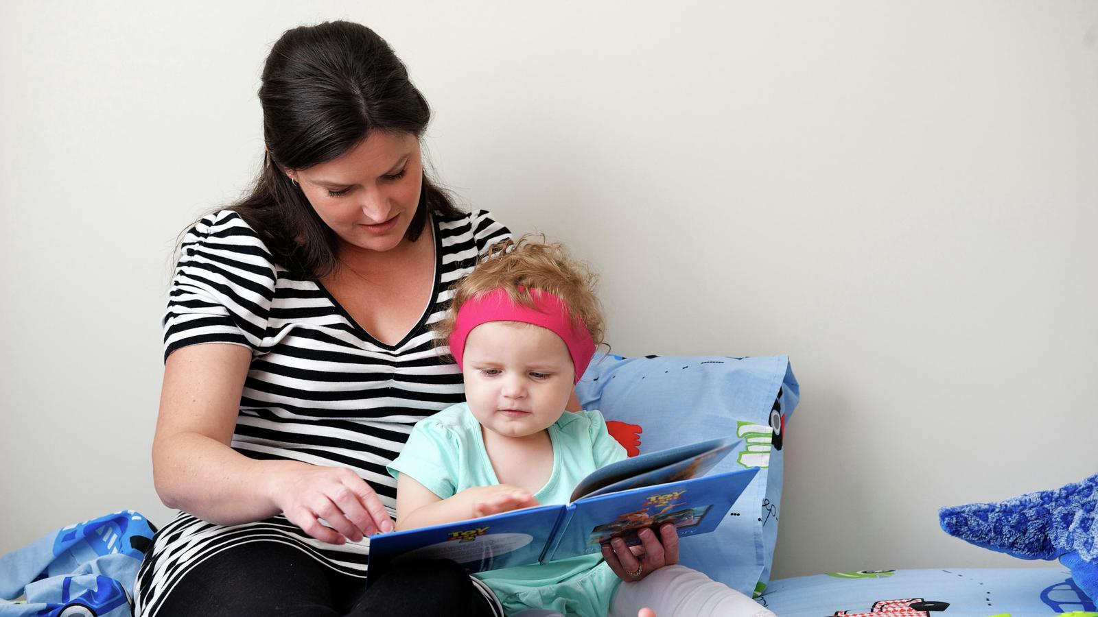 A woman reads a book to a child wearing a hearing device