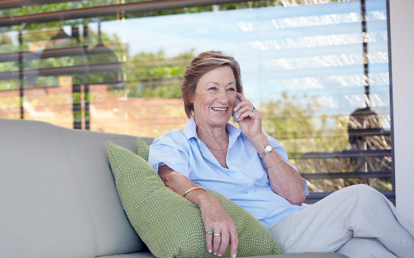 An elderly woman chats on a phone as she sits on a couch