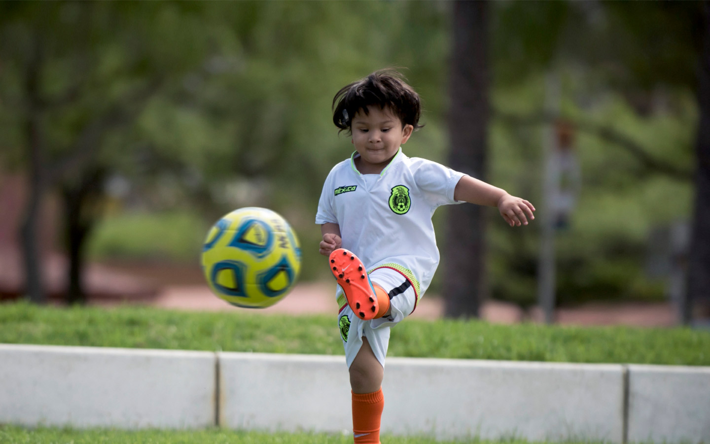 Child playing soccer with baha sound processor