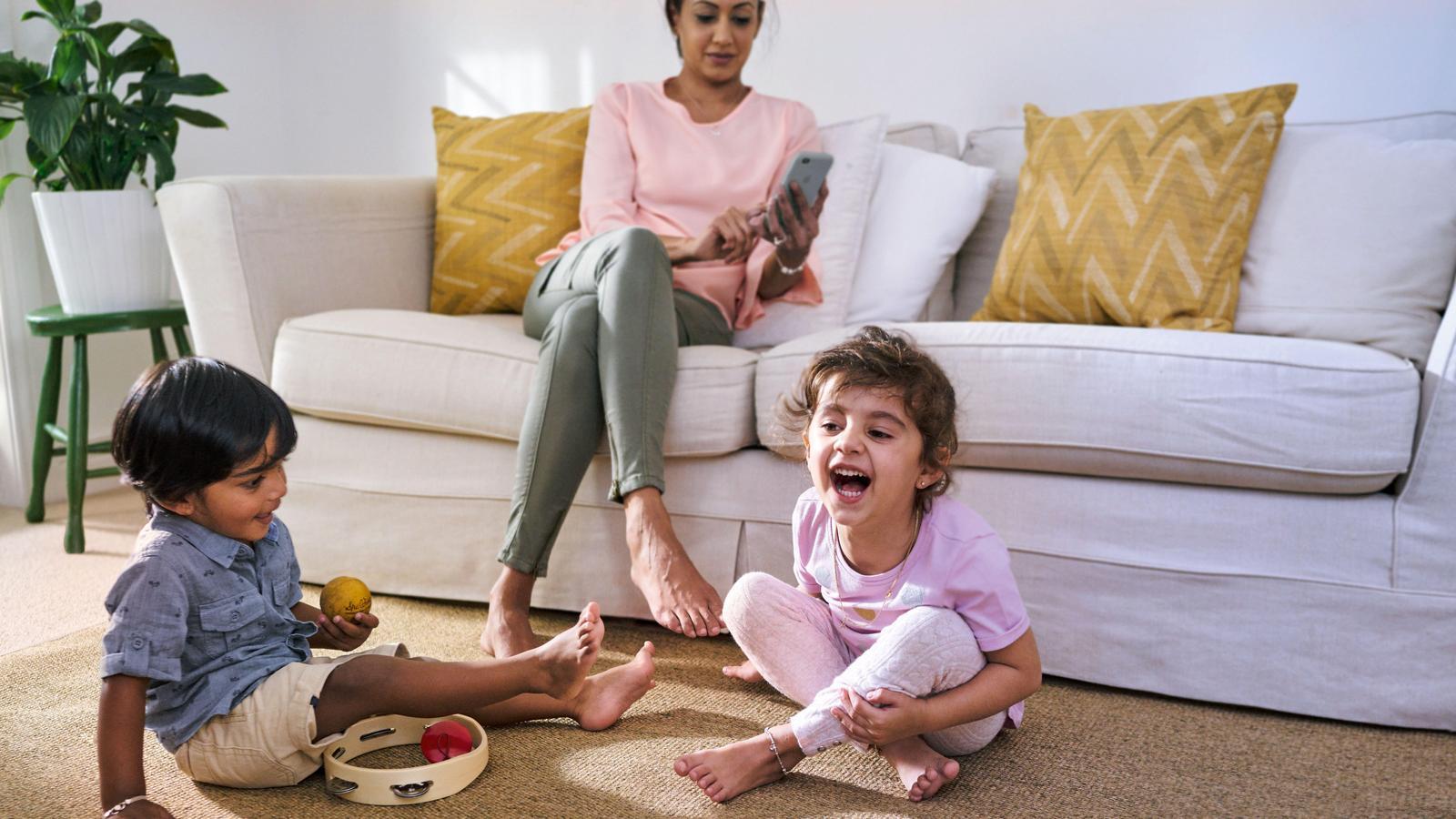 Två barn leker i vardagsrummet medan deras mamma tittar på