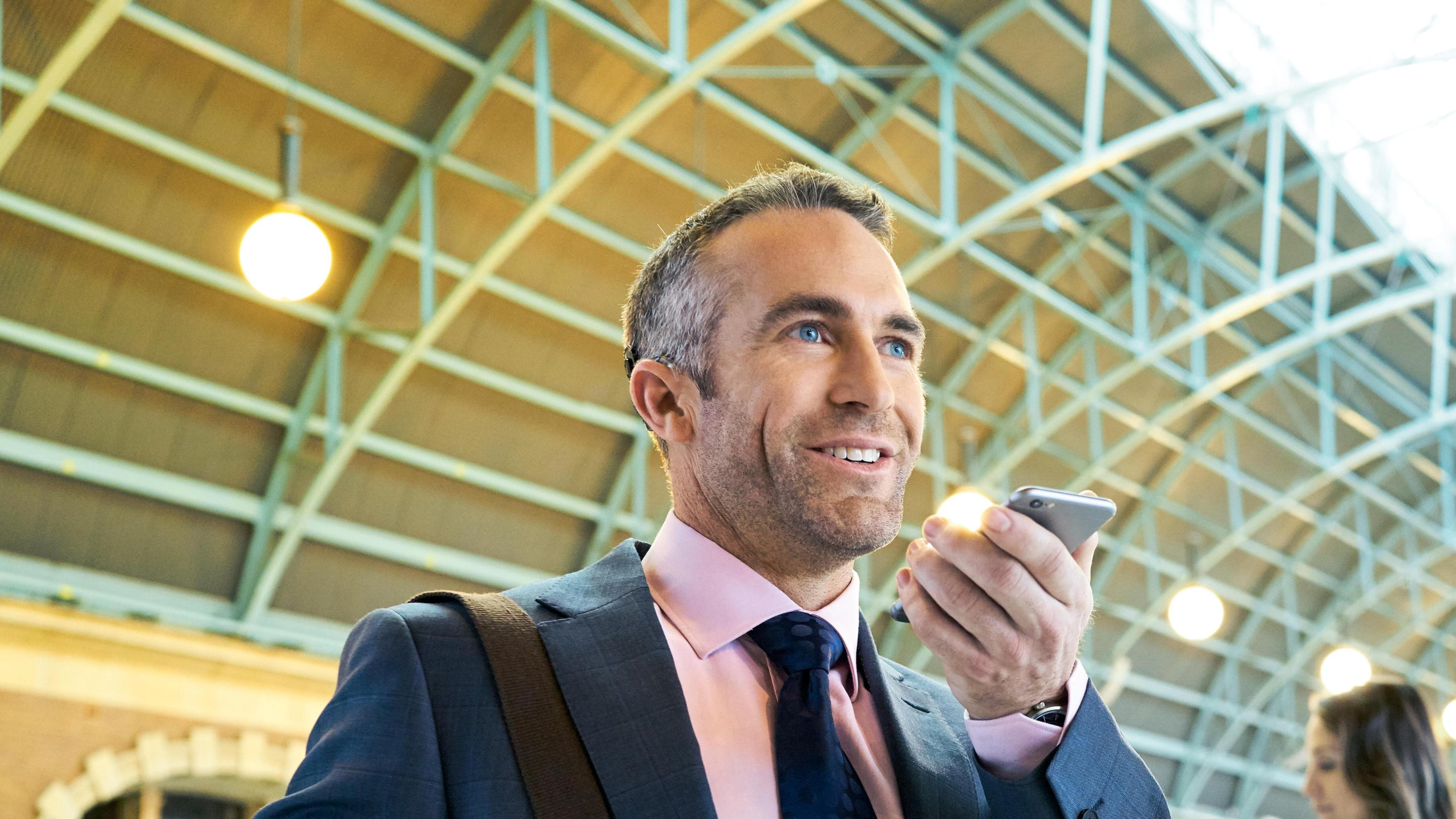 A man wearing an implant chats on a smartphone