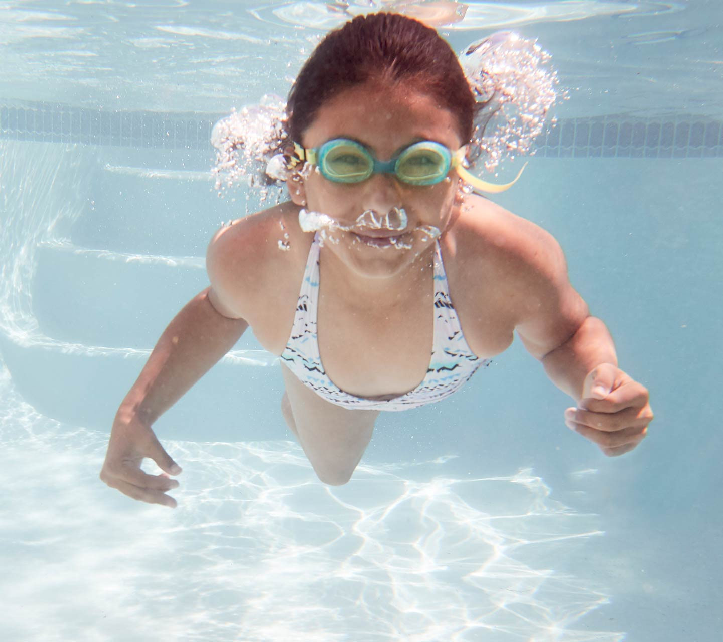 Child swimming underwater with Cochlear implant