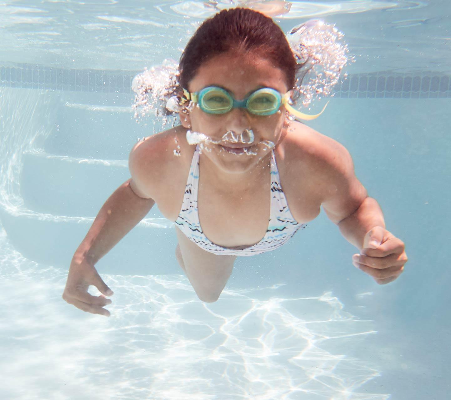 Copil cu implant Cochlear înotând sub apă