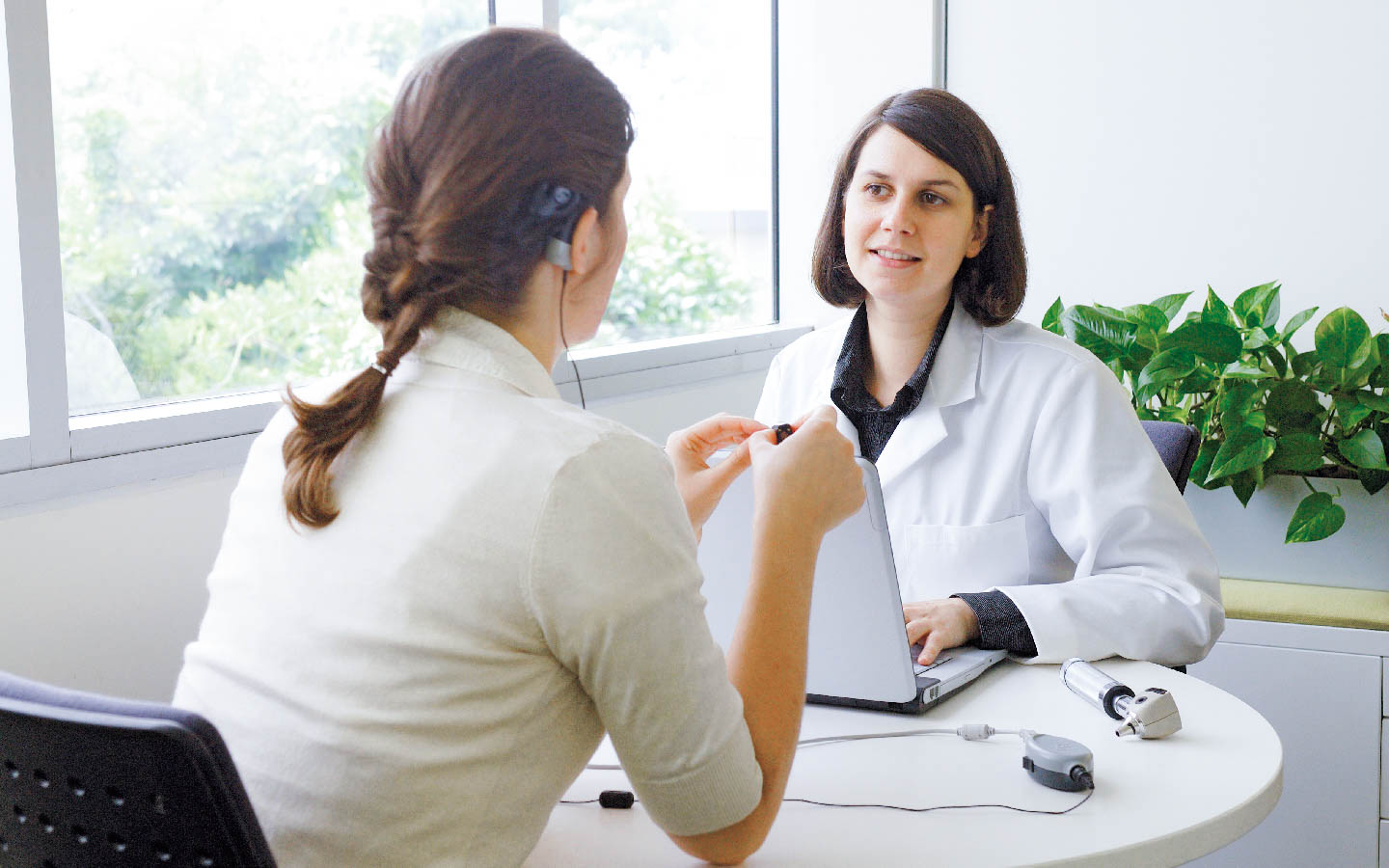 An audiologist conducts a hearing test with a patient