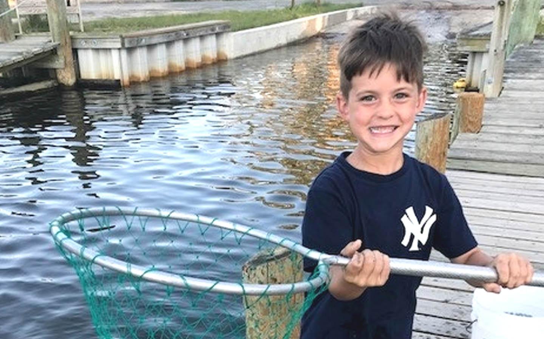 Il portatore di impianto Nucleus Sean posa per una foto con una rete da pesca