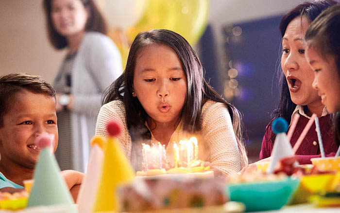 Young girl with Cochlear implant blowing her birthday cake wiht family