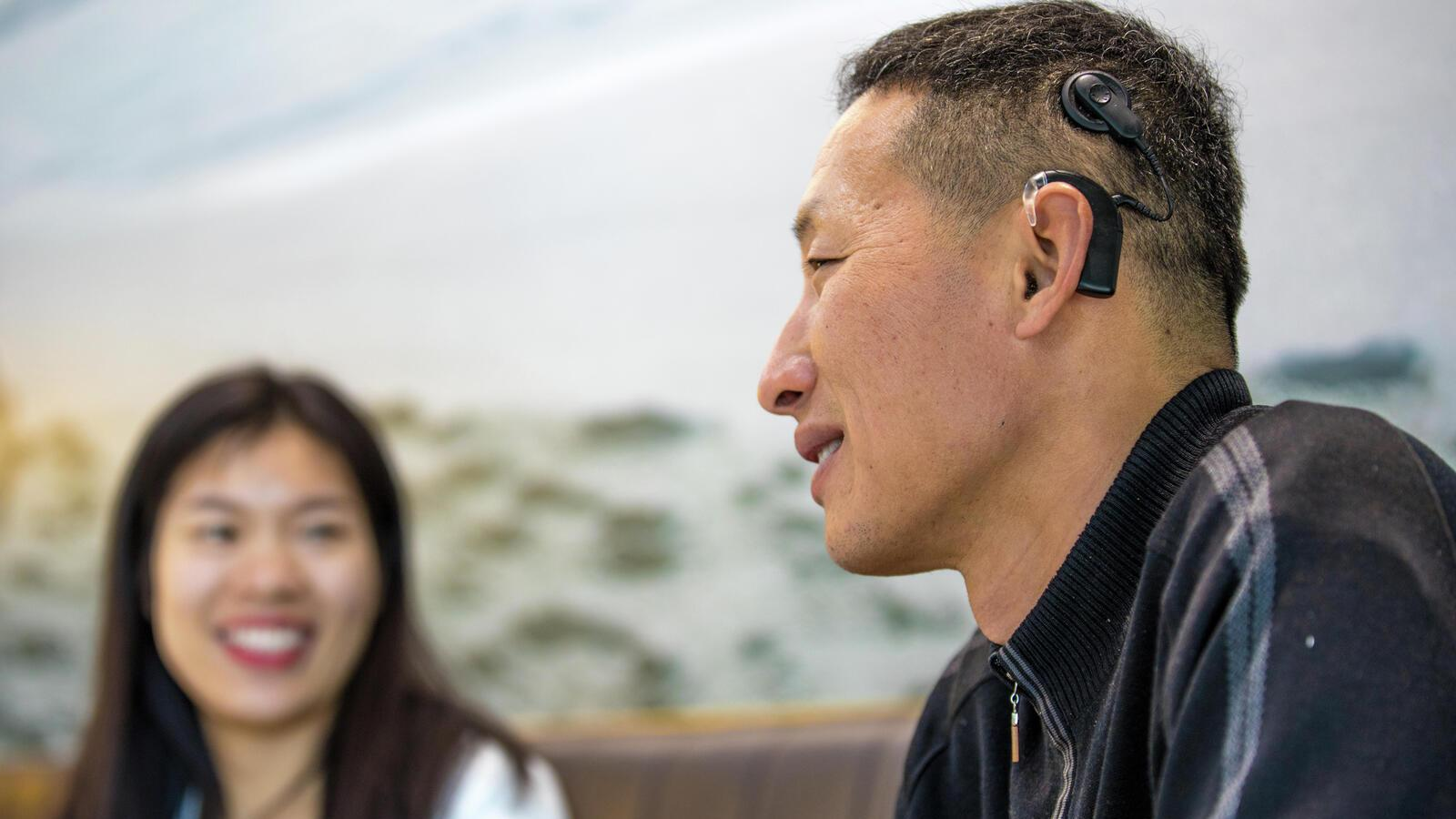 A mother and father sit on a couch with son, wearing a Cochlear implant, and listen to him read