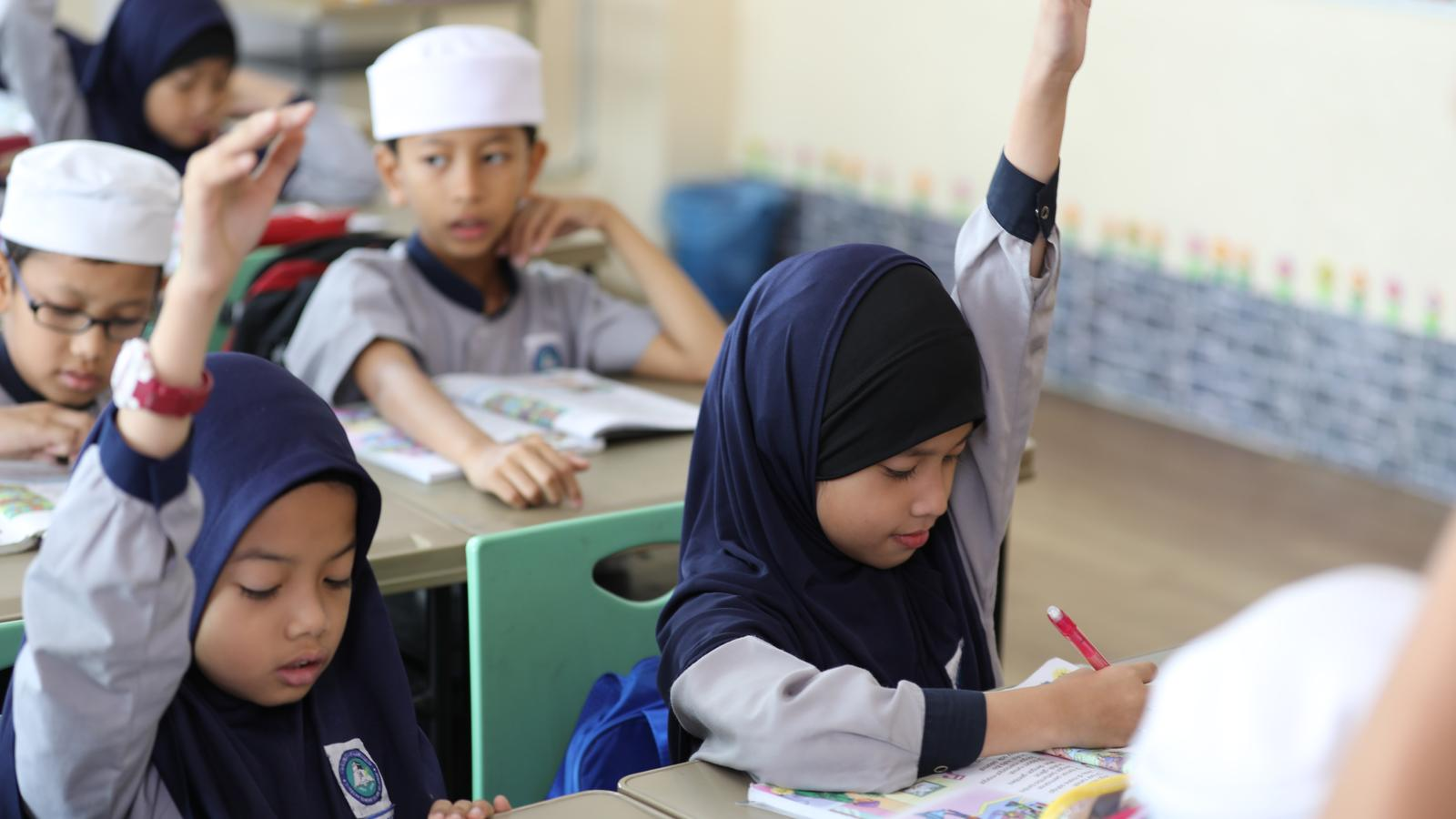 A child raises her hand in her classroom