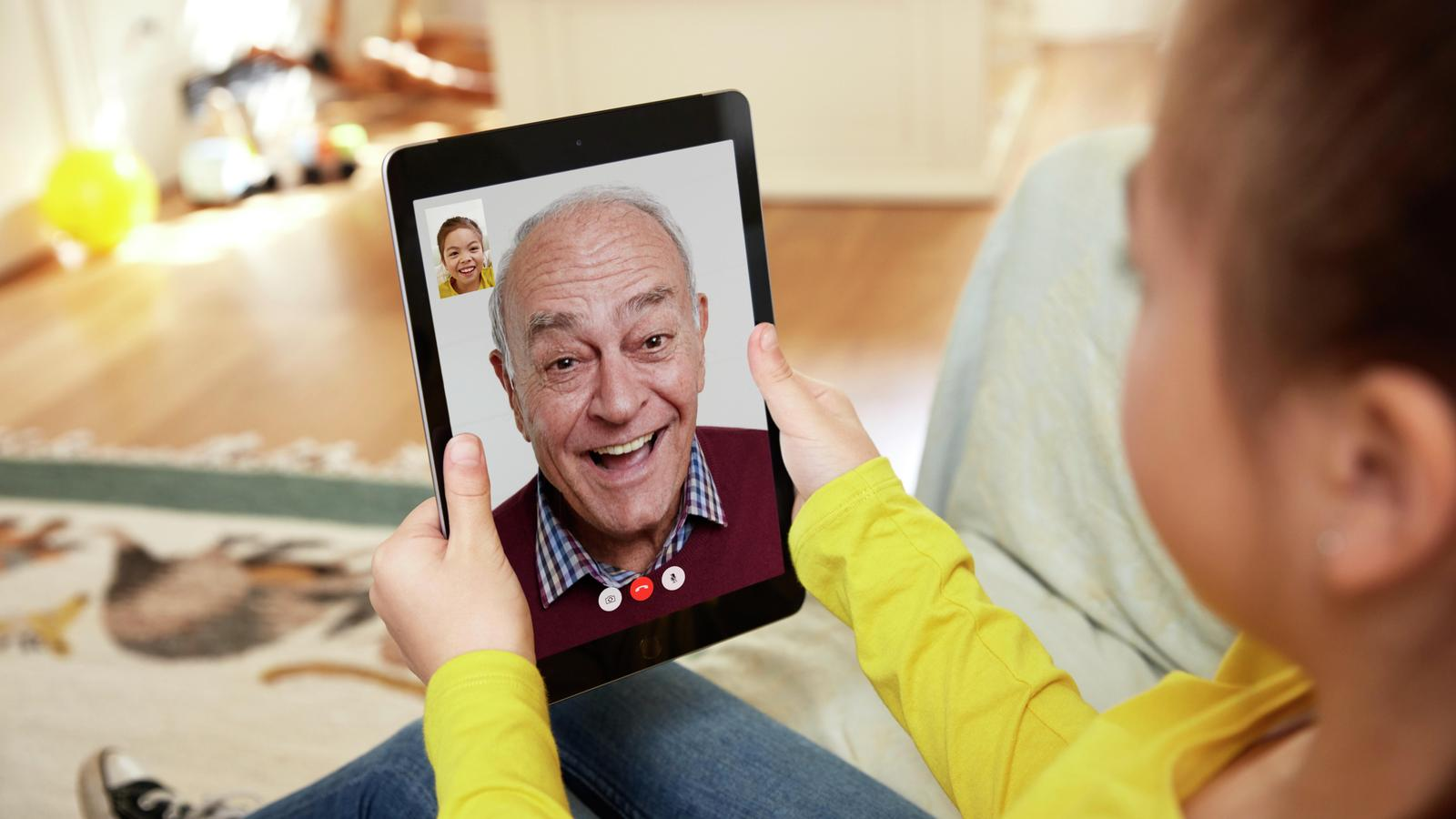 A man appear on an iPad chat with his granddaughter