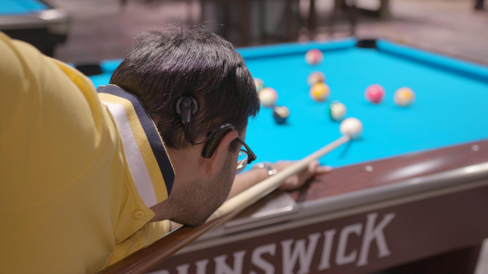 Adult man wearing an implant plays snooker