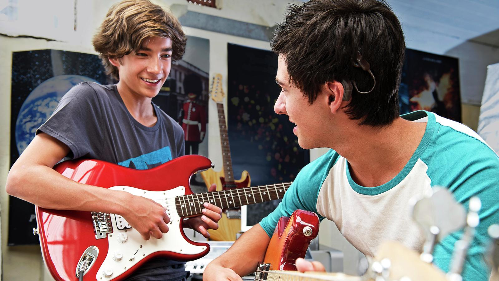 Cochlear recipient Christopher plays guitar with a friend