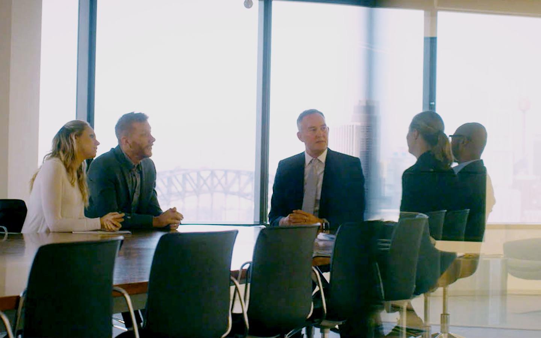Cochlear CI-Träger Tobin bei einer Bürobesprechung im Gespräch mit Angestellten