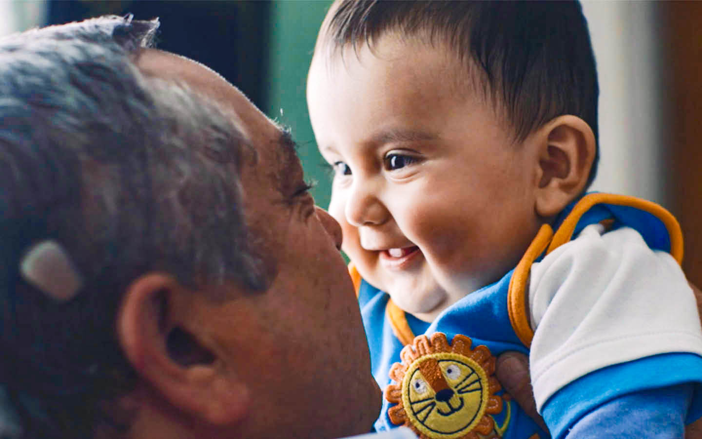 A man holds up his smiling grandson