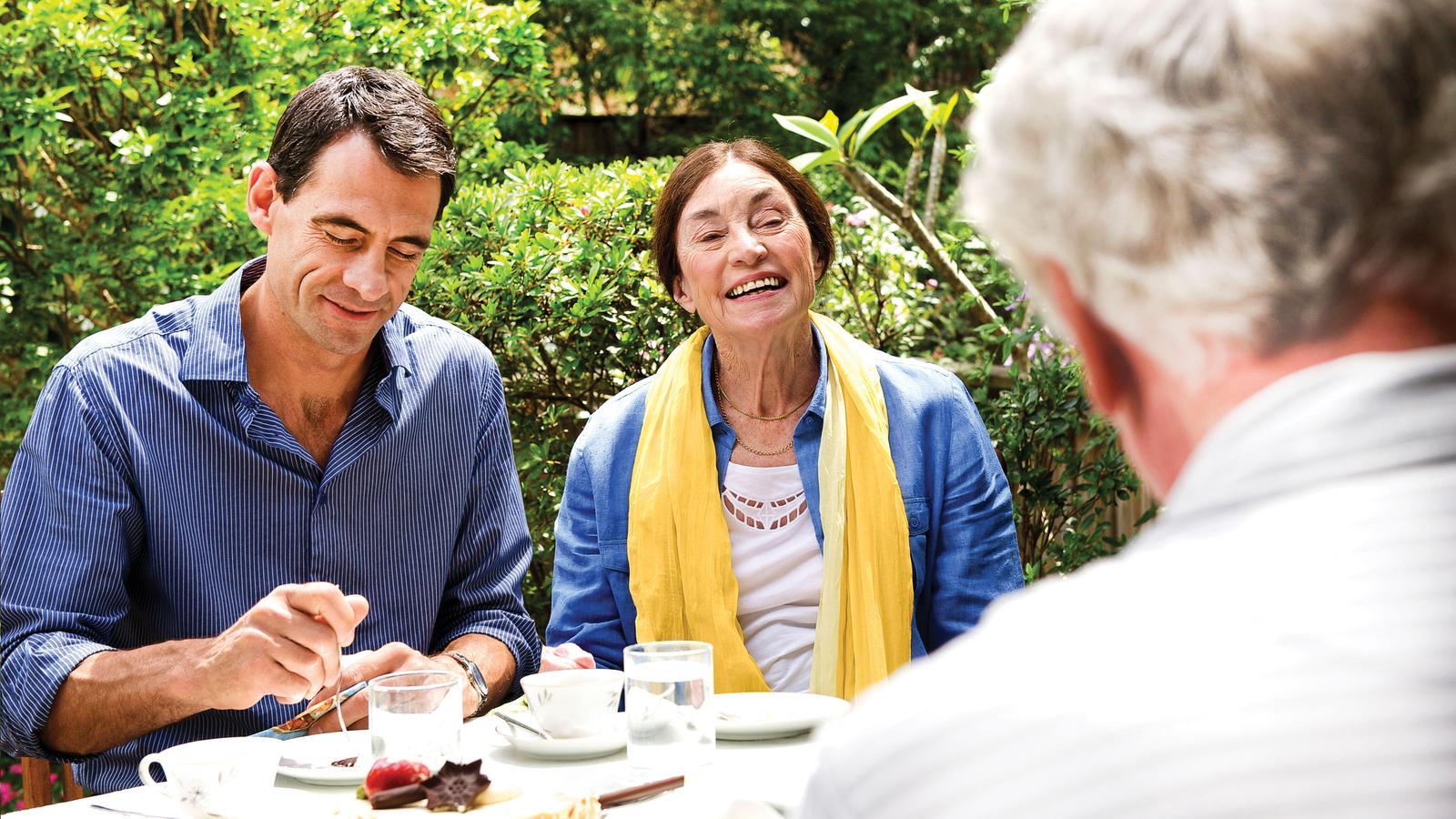 Tres adultos comparten un almuerzo en el jardín