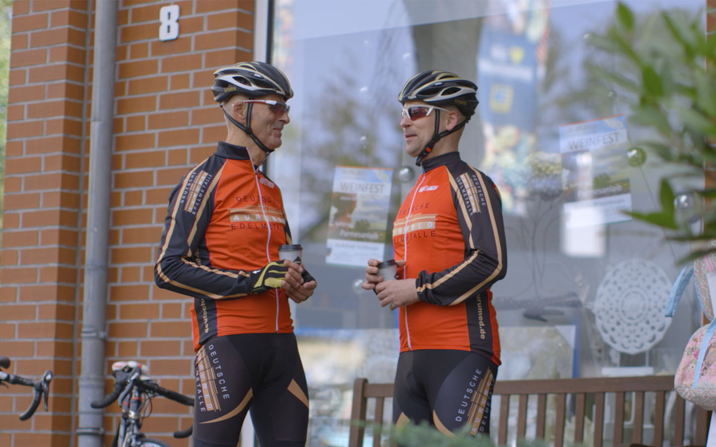 Two men wearing cycling attire chat as they hold coffee cups