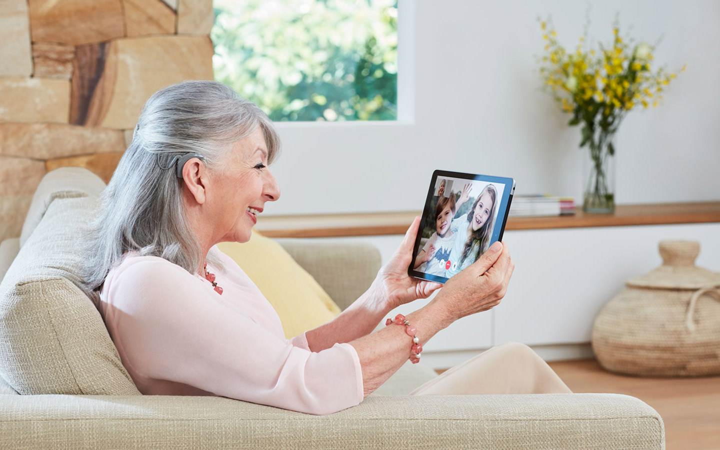 A woman with a Cochlear implant uses an iPad